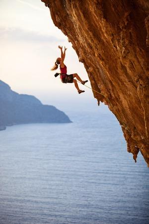 Foto de Female rock climber falling of a cliff while lead climbing - Imagen libre de derechos