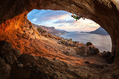 Male rock climber climbing along a roof in a cave at sunset