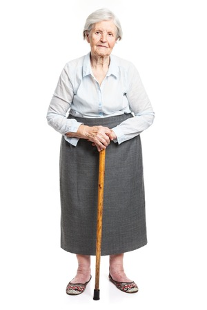 Foto de Senior woman with walking stick standing over white - Imagen libre de derechos