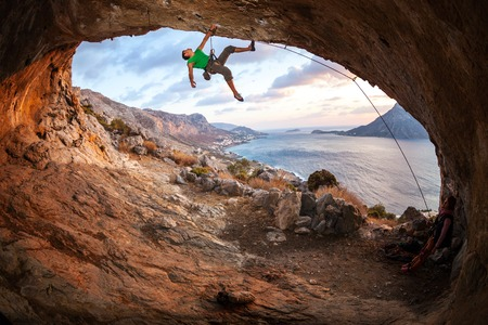 Male rock climber climbing along a roof in a cave at sunset. Kalymnos Island, Greece
