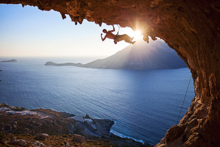 Foto de Male rock climber climbing in cave with beautiful view in background - Imagen libre de derechos