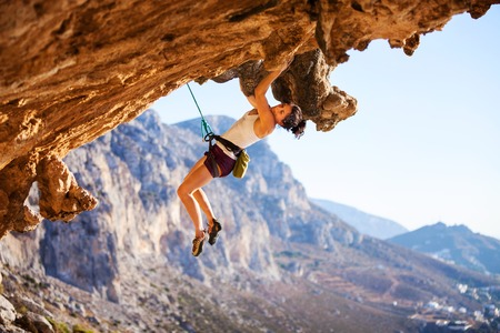 Photo for Young female rock climber on a face of cliff - Royalty Free Image