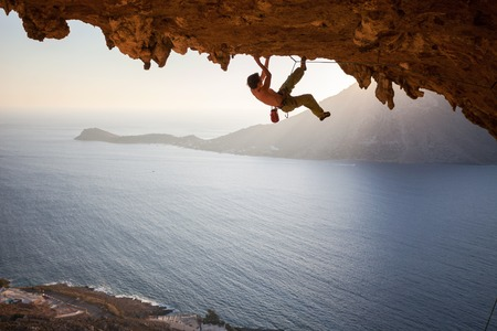 Rock climber climbing along a roof in a cave at sunset