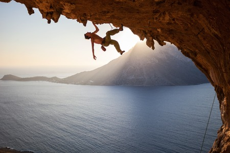 Rock climber climbing along a roof in cave at sunset