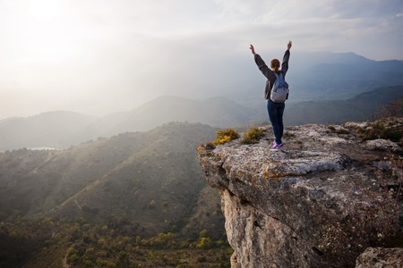 Foto de Young woman standing on cliff with outstretched arms and enjoying valley view - Imagen libre de derechos