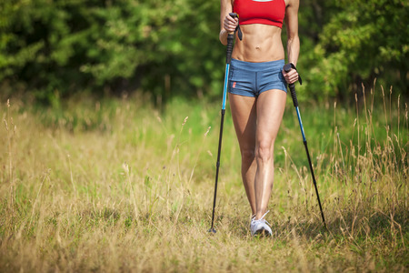 Photo for Fit young woman hiking with nordic walking poles in summertime - Royalty Free Image