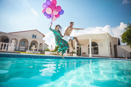 Photo pour Happy young couple jumping into the pool while holding a bunch of balloons - image libre de droit