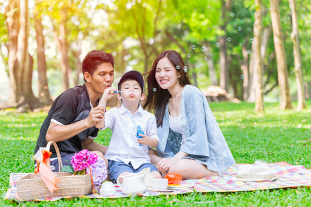 Foto de Asian teen family happy holiday picnic moment in the park - Imagen libre de derechos