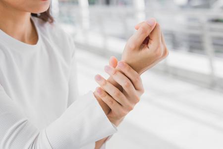 Foto de closeup business women holding rub her wrist pain from using computer. Office syndrome joint pain by occupational disease. - Imagen libre de derechos