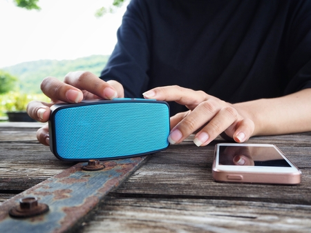 Foto de Woman using wireless speaker with smart phone - Imagen libre de derechos
