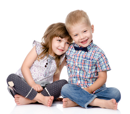 Photo pour Smiling brother and little sister hugging  isolated on white background - image libre de droit