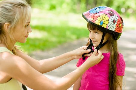 Photo pour young mother dresses her daughter\'s bicycle helmet - image libre de droit