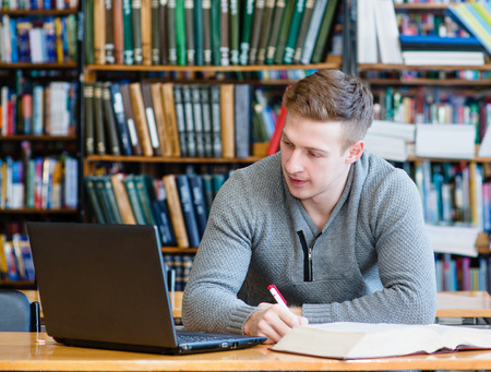 Photo for Male student with laptop studying in the university library - Royalty Free Image