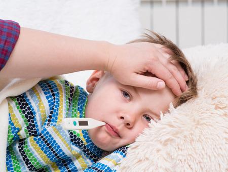 Foto de Sick kid with high fever laying in bed and mother taking temperature - Imagen libre de derechos