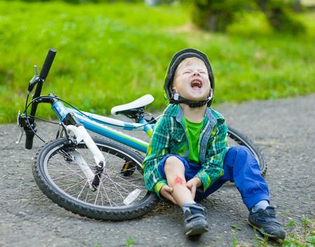 Foto de boy fell from the bike in a park. - Imagen libre de derechos
