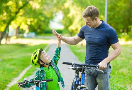 Foto de father and son give high five while cycling in the park - Imagen libre de derechos