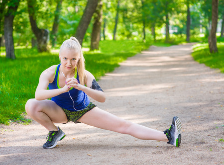 Young fitness woman runner stretching legs before run.