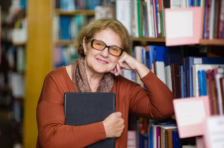Foto de Smiling elderly woman with book in library. - Imagen libre de derechos