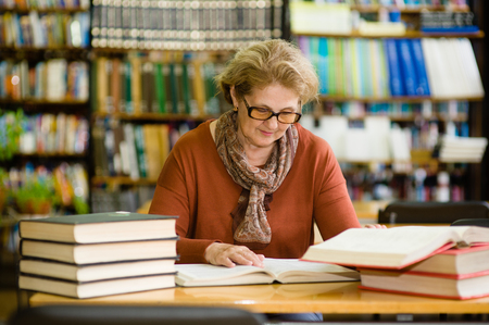 Photo pour senior woman reading a book in the library. - image libre de droit