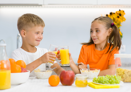 Photo pour Girl and boy clink glasses with orange juice at breakfast. - image libre de droit