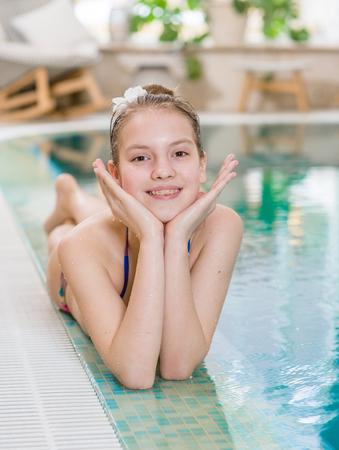 Photo pour Happy teen girl lies near the pool. - image libre de droit