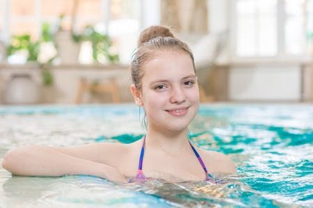 Photo pour Smiling beautiful teen girl in the pool. - image libre de droit