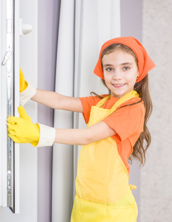 Foto de Happy little girl cleaning window with rag. - Imagen libre de derechos