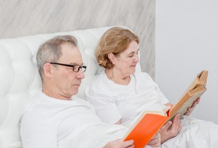Photo pour elderly couple reading a book on the bed. - image libre de droit
