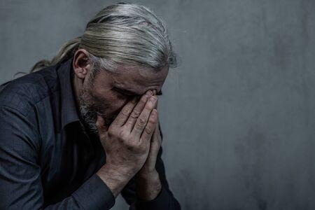 Foto de Senior man covering face and crying on dark background. Empty space for text. - Imagen libre de derechos