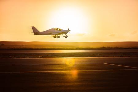 Photo pour small plane on the runway background of sunrise - image libre de droit
