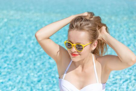 Photo pour Summertime in pool. Young woman with yellow sunglasses in pool. - image libre de droit