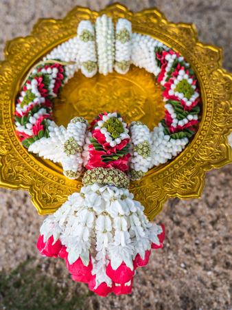 Foto de Garland, lei of flowers on tray with pedestal for worship - Imagen libre de derechos