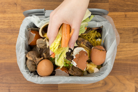 Photo for Overhead of a hand placing food scraps into a garbage bin - Royalty Free Image