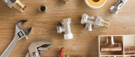 Photo for Wide format image of pipes, fittings, and plumbing tools on wooden surface - Royalty Free Image