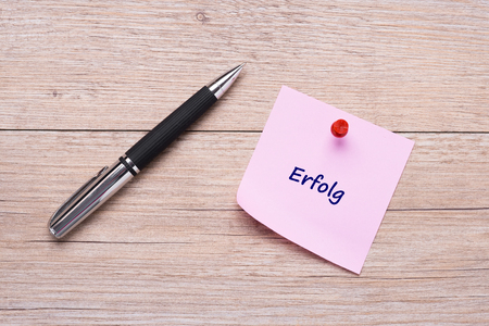 German word Erfolg on pink sticky note with red pin on wooden board