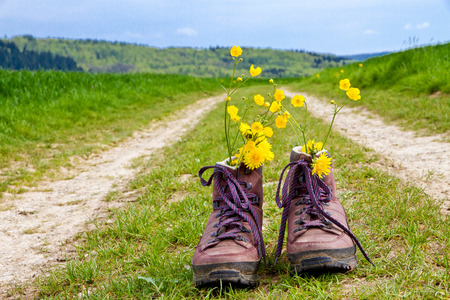 Photo pour Hiking boots on a country lane - image libre de droit