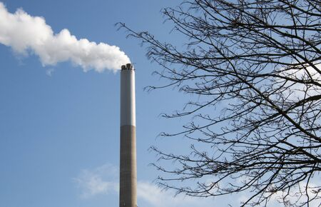 Foto de White smoke comes out of a smoking chimney - Imagen libre de derechos