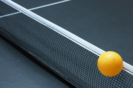 Table tennis ball going over the net