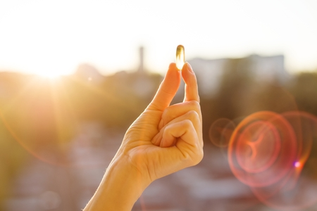 Foto de Hand of a woman holding fish oil Omega-3 capsules, urban sunset background. Healthy eating, medicine, health care, food supplements and people concept - Imagen libre de derechos