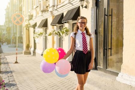 Foto de Girl teenager high school student with balloons, in school uniform with glasses goes along the city street. Start of classes. - Imagen libre de derechos