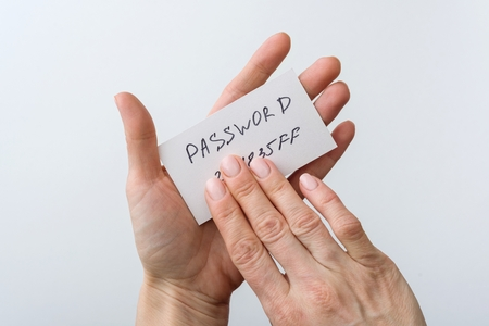 Photo for Woman's hand holds a password on paper, that covers the password with finger. - Royalty Free Image
