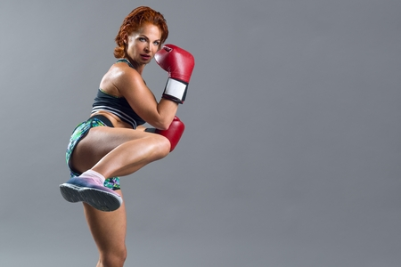 Photo pour Athletic mature woman boxer with red gloves in sports clothes, guarding herself, getting ready to attack. Gray studio background, copy space - image libre de droit