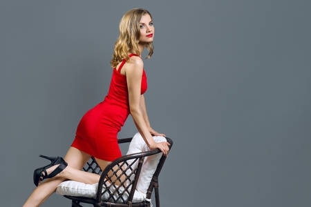 Foto de Fashionable young blonde girl in red dress on gray - Imagen libre de derechos