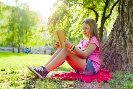 Photo pour Girl child in glasses reading book in the park, on the grass near the tree - image libre de droit