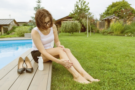 Foto de Mature businesswoman after a working day sits near the home pool. She took off her shoes and smeared her feet with soothing foot cream - Imagen libre de derechos