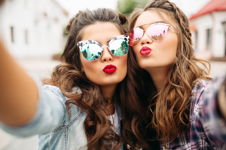 Photo pour Gorgeous brunette girlfriends with hairstyle, mirrored sunglasses and red lips making selfie with duck face. - image libre de droit
