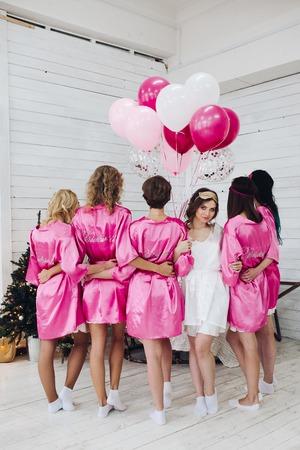 Foto de Full length of bride in white robe with bridesmaids standing bac - Imagen libre de derechos