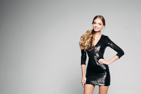 Foto de Beautiful, cute blonde in evening mini dress cute smiling looking at camera. Girl with makeup, low-key hairdress prepare for the party. Isolated on a gray background. - Imagen libre de derechos