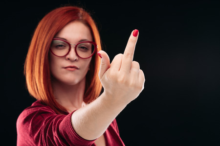 Foto de Confident and angry red haired girl showing finger, gesturing fuck off. - Imagen libre de derechos