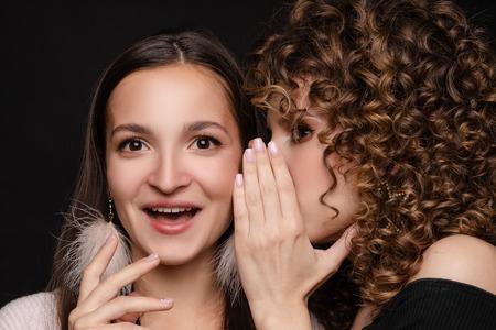 Photo for Shocked brunette posing while friend whispering secret - Royalty Free Image